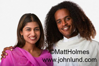 Happy smiling ethnically diverse couple, she being Indian and he being African american. She is wearing purple and he is wearing white.